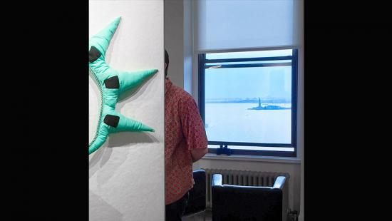 Someone looking at art in an exhibition, with a view of the Statue of Liberty through a window in the background.