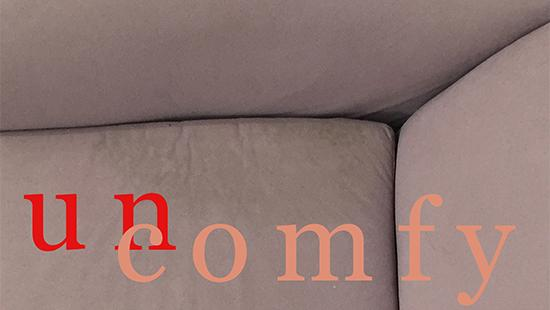 Close up image of a couch cushion with the words 'un comfy' written across it.