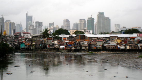Milan skyscrapers in background with slums along the water.