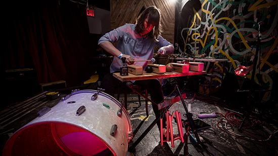 Artist playing a mallet musical instrument with wind chimes and drum with a graffiti background.