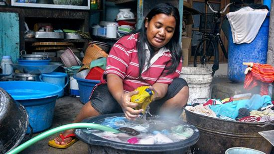 A woman in Surakarta, Indonesia washes clothes in her dwelling courtesy of a nearby garden hose.