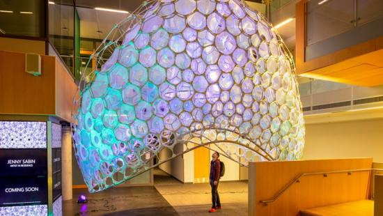 A person looks up from under a colorful, dome-shaped lattice structure in a gallery space.