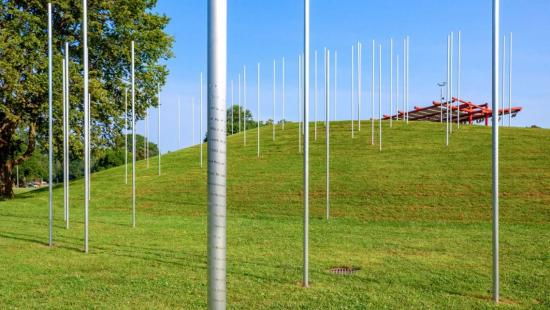 A series of large silver poles protruding from a grassy field with a red structure in the distance.