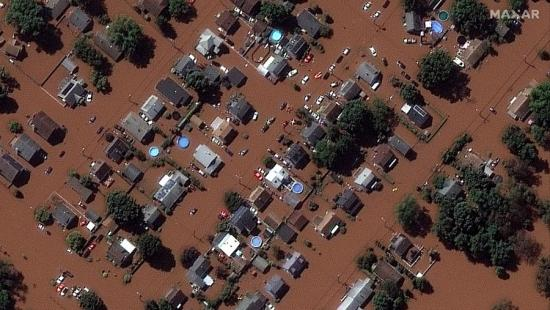 A neighborhood of single-family homes flooded with brown storm water.
