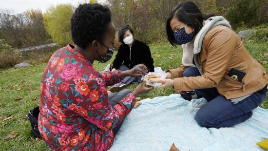 Three people seated on a blanket on green grass sharing food.