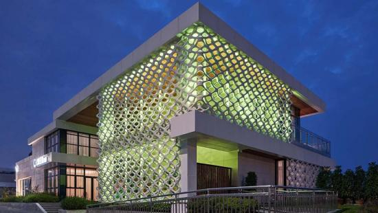 A two-story building faced with lattice panels backlit with green lighting.