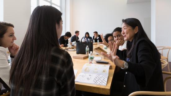 Architecture students sitting around a table discuss their portfolios with firm partner