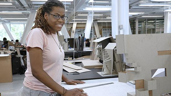African-American female student working with architectural models in a studio