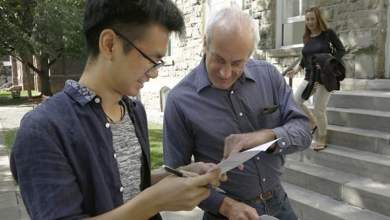 college student and professor talking outside a grey brick building