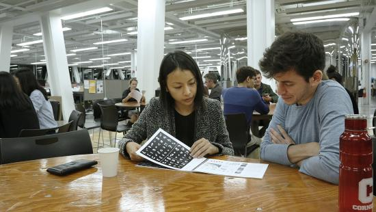 Two people seated at a table looking at a book in a modern building