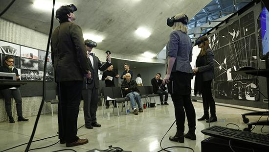 students and faculty wearing virtual reality goggles as a student presents