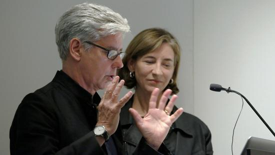 a man and a woman speaking into a microphone