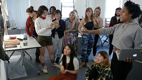 several young people looking together at artwork in a studio