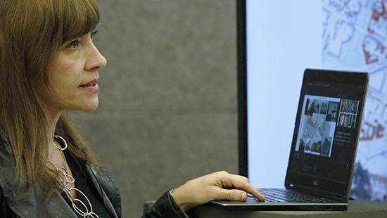 A woman with long dark hair at a podium using a laptop in front of a large lighted screen
