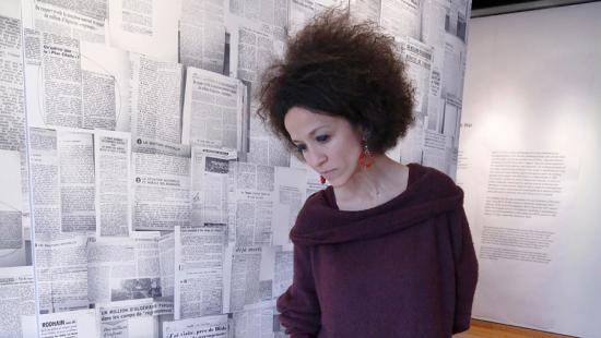 A person looking down next to a wall covered with hanging newspaper clippings.