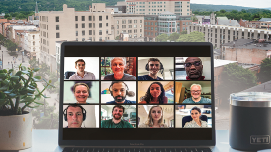 A laptop screen with faces in boxes, city buildings, distant hillside.