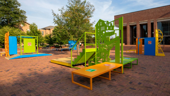 Colorful metal play structures on red bricks next to a brick building.