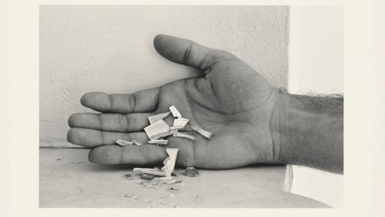 Small chips of wood or paper falling from an open hand.