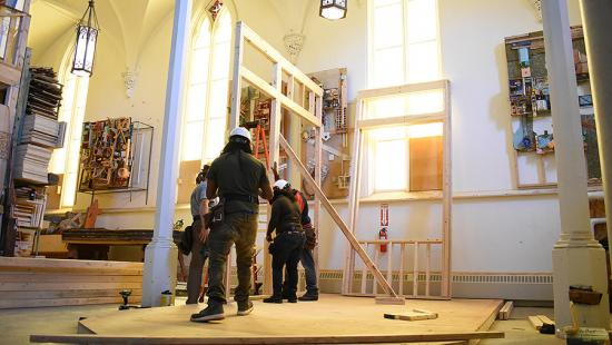 Four people in construction gear in the interior of a church.