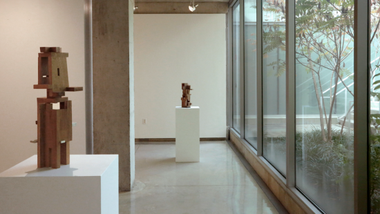 Abstract wooden sculpture piece with various sized rectangular pieces put together in a gallery space.