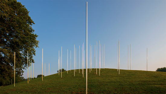 58 vertical metal poles set on a grassy mound, blue sky.