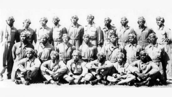 3 rows of men seated and standing dressed in World War II pilot gear.
