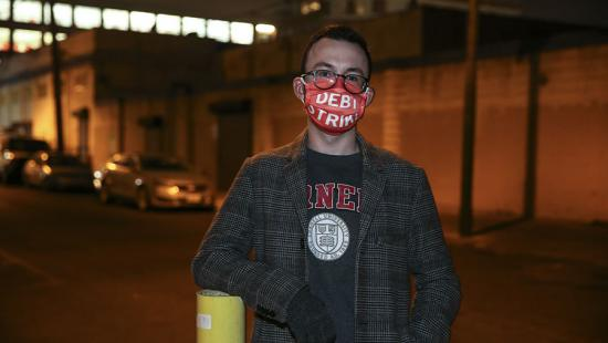 A man wearing a face mask, city street at night.