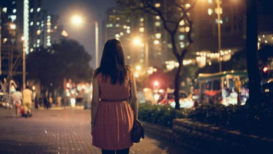 A woman walking in a city at night