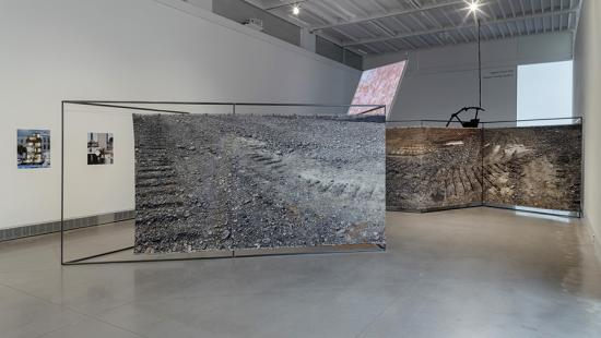 Two large textile pieces suspended from metal frames in a gallery space.