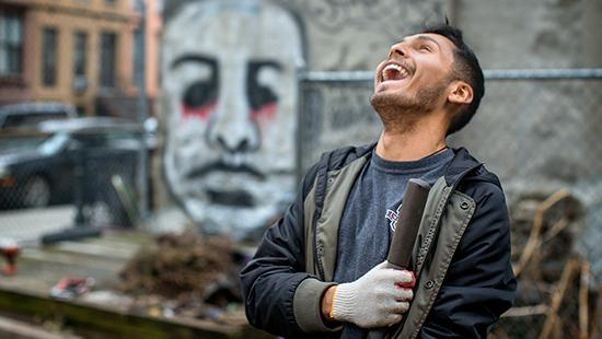 student laughing and holding a trowel in front of a wall with a painting on it