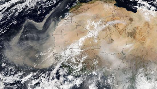 A satellite view from space of the African continent through clouds.