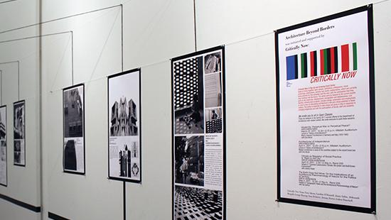 exhibition shot of black and white and colored posters on a wall with black tape above and below