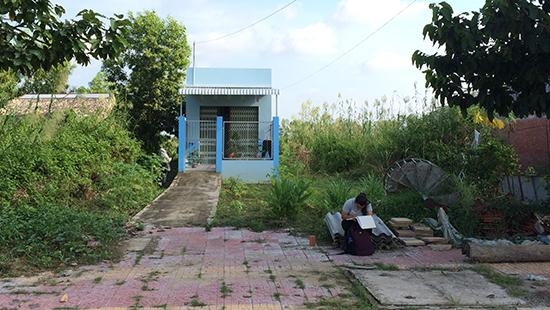 student writing in a pad in front of a blue house in the tropics