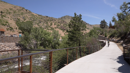 Person bicycling on a concrete path with metal railing, hill covered with scrub grass.