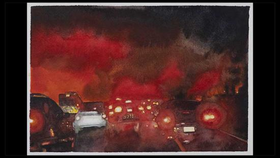 Many cars on a road at night with smoke and fire in the sky.