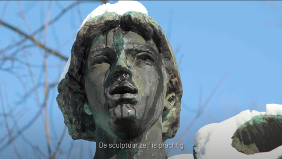 Statue of a person's face with snaow and blue sky.