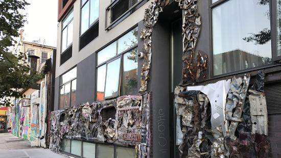 Storefront on a city street with a raised motif sculpture applied to it.