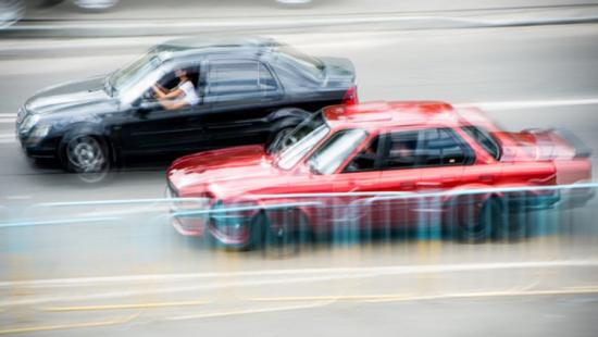 Two cars speeding on a road.