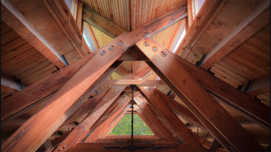 Wooden beams and panelling on a ceiling, a triangular window, metal deatils.