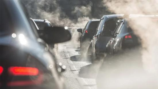 Automobiles and exhaust fumes on a divided highway.