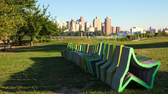 A uniform row of brightly colored concrete shapes on a lawn with a city skyline in the background