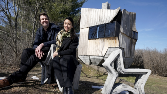 A man and woman sitting side by side in front of a rural cabin