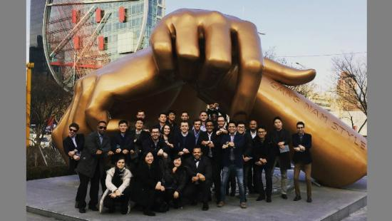 A group of college students and faculty pose under the Gang Nam Style sculpture in Seoul, South Korea