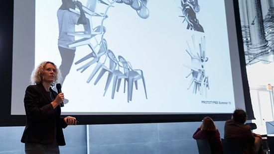 Caroline O'Donnell speaking into a microphone in front of a screen with an illustration on it