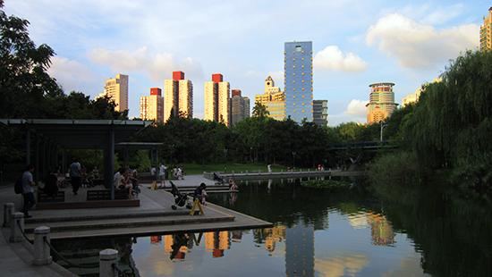 pond and dock surrounded by trees with a city skyline in the background