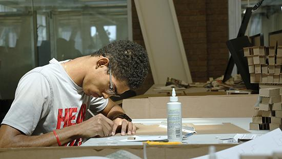 student in studio working at a desk with glue and cardboard models