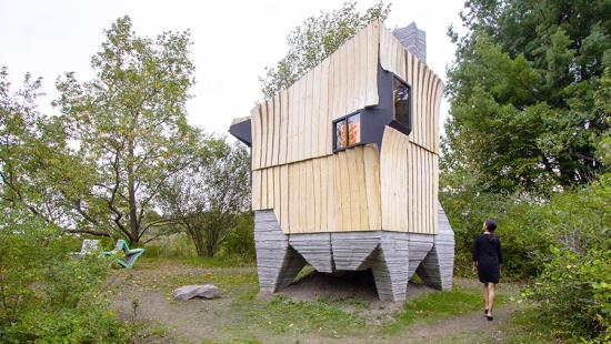 Rough wood-sided cabin on asymmetrical concrete piers, trees, a person walking.