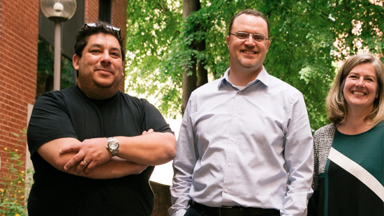 Three people standing together, a brick building, trees.
