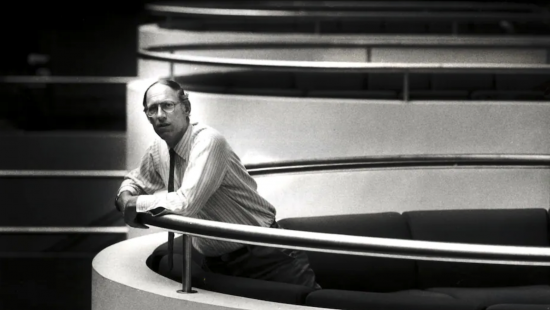 Person leaning on a curved balustrade in a modern interior space.