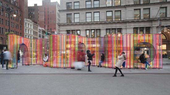A wavy wall of colorful translucent material on a city street.